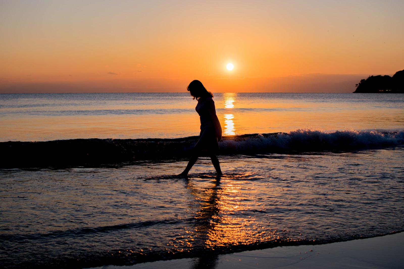 たそがれる女性夕焼けの浜辺