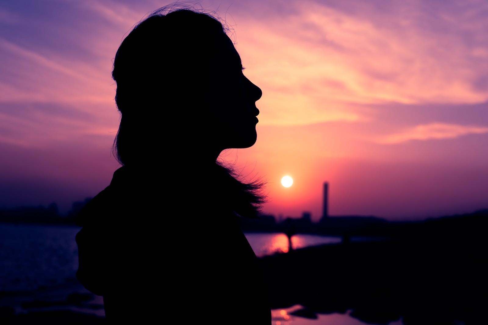夕焼けに黄昏る女性